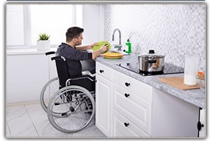 SPECIALTY SERVICES: Man in wheelchair washing dishes in modified kitchen